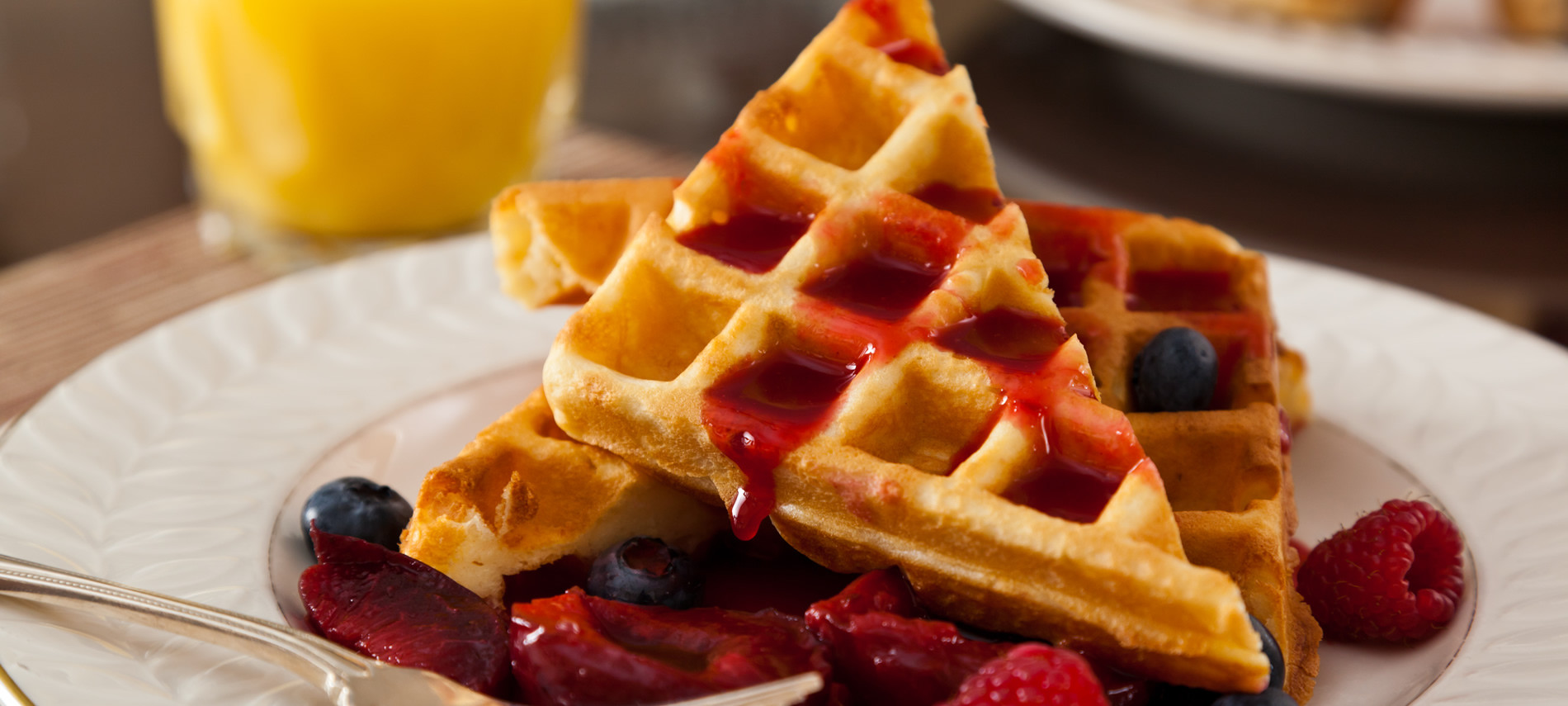 Plate with sliced waffle with Red Raspberries and BLue Berries