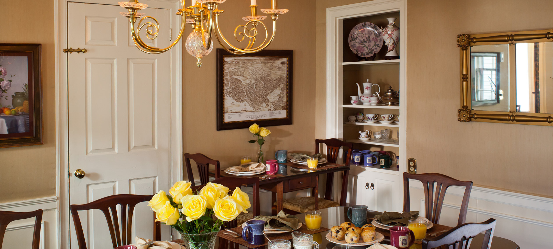 View of the Dining room with the table set for breakfast, juice, coffee, muffins and a vase with yellow roses