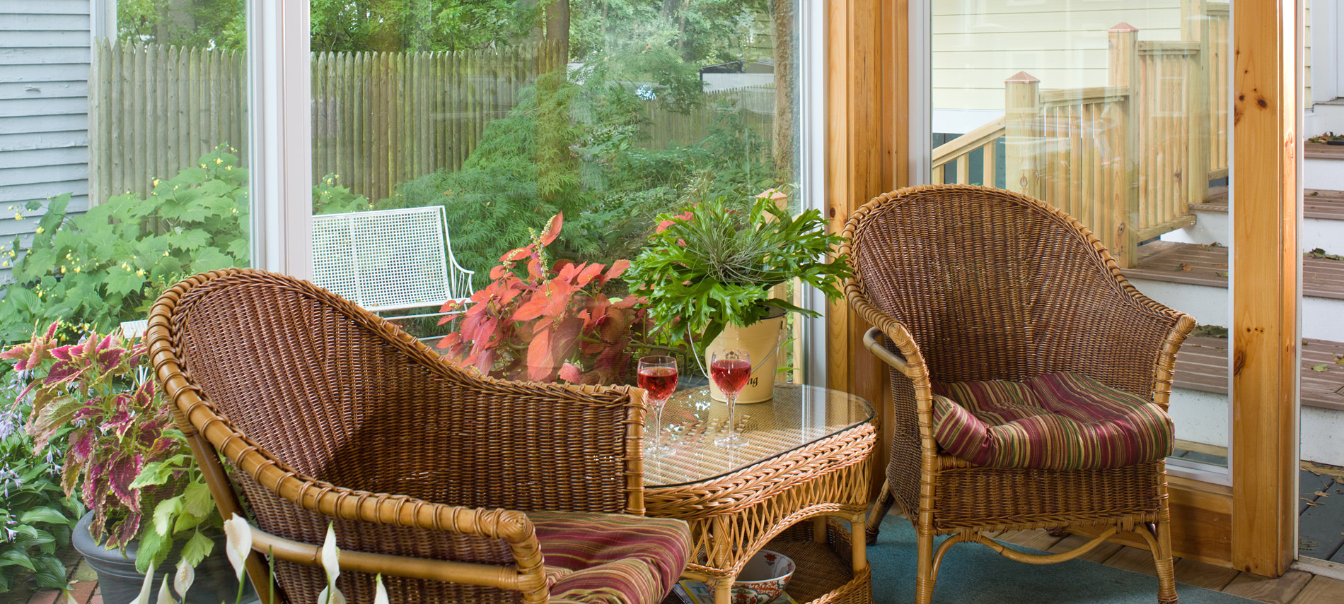 Two Wicker Chairs with table in the center with two wine glasses with Red Wine