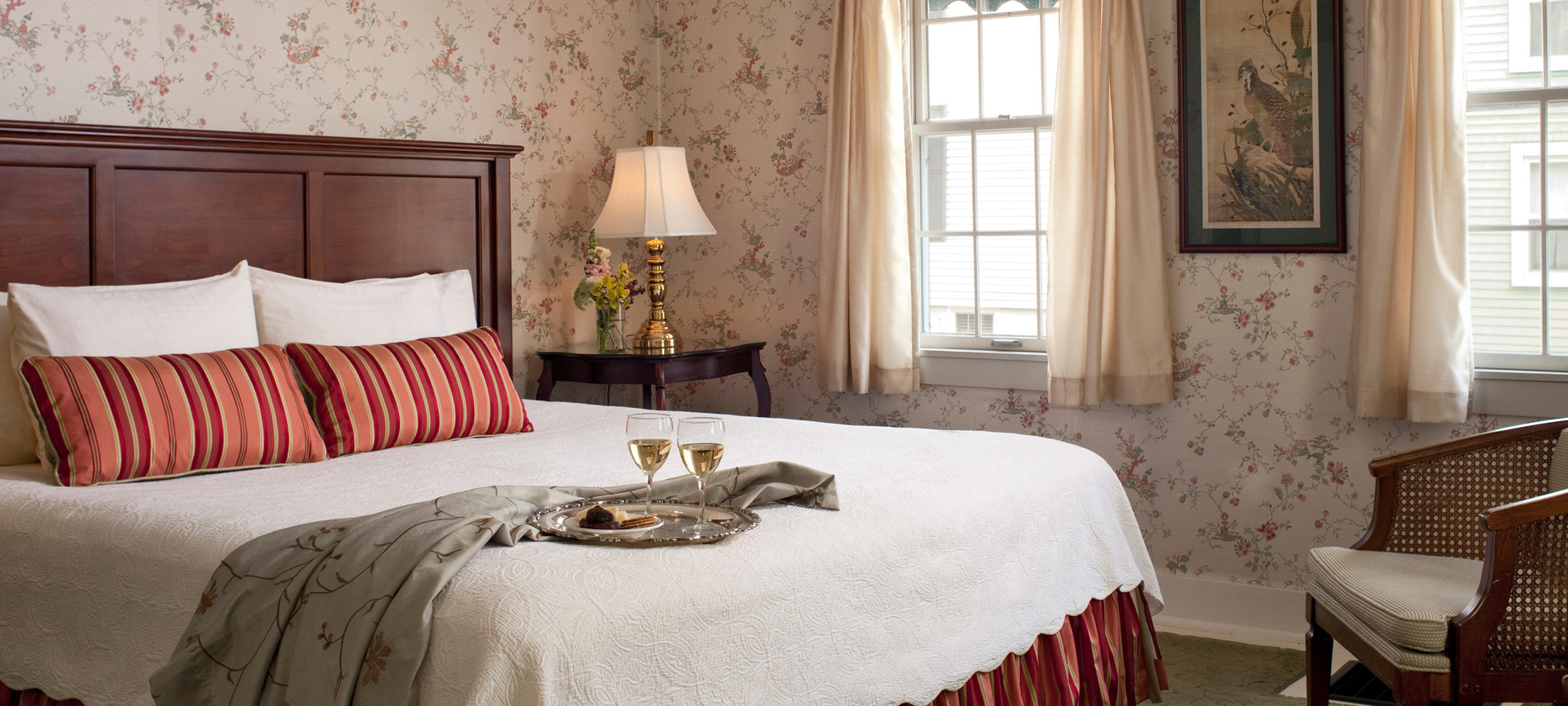 Plush King size bed with a white comforter, Flower Wall paper. ON the bed is a tray with two glasses of white wine.