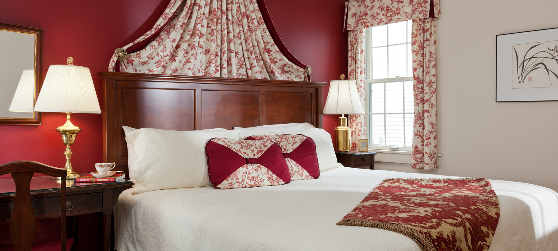 View of the Kings size bed with a white comfortor. Deep Red wall with white and red flower fabric from the head board to the ceiling to match the curtains on the wall