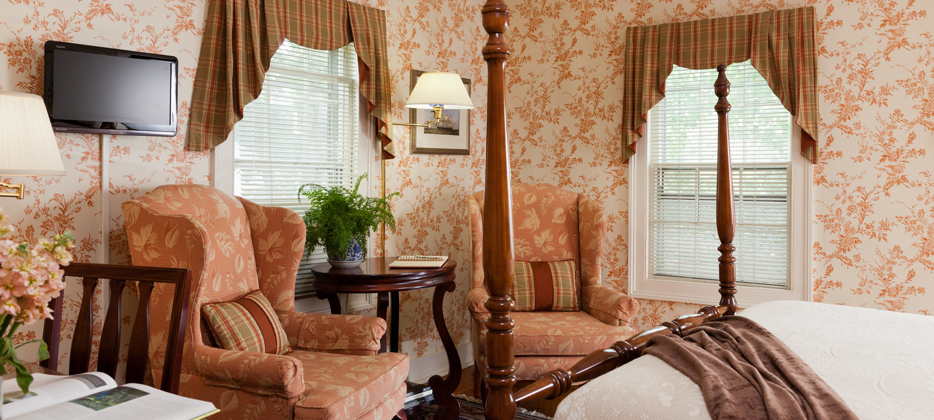 Typhoon Room with two peach high back chairs and peach flowered wall paper.