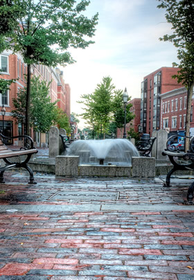 Water fountain in the middle of Market Square with green trees and brick buildings lining the street