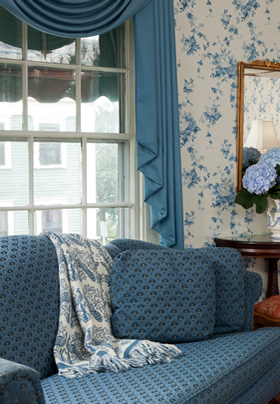 A blue pattern Love seat in front of a window with Hydrangeas sitting on the end table.