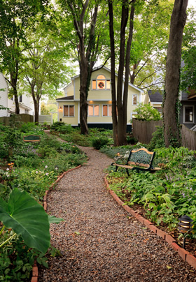Walk way thru the green gardens in the backyard with relaxing benches to sit and enjoy