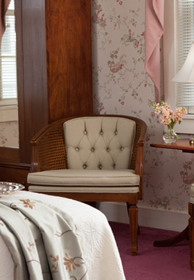 Corner of the bed with a white comforter, flowered wall paper, low fabric antique chair in tan colors