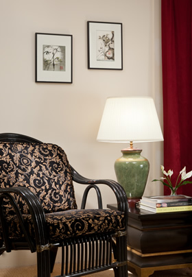 Black chair with black and gold Tapestry fabric cushions, green lamp on the unique side table.