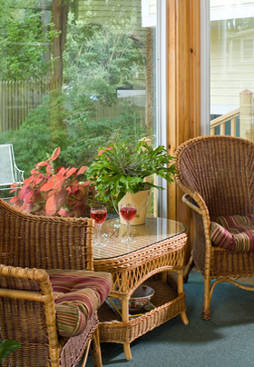 Tan wicker chairs and table with striped fabric cushions. two glasses of Wind on the table with two green plants
