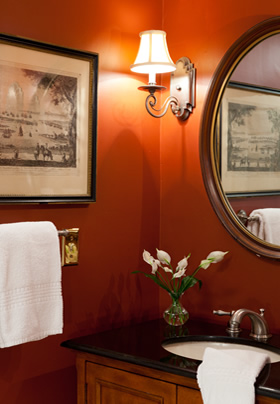 Rust color walls in this bathroom with a black marble top. White towels and white flowers