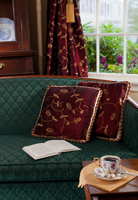 Green paisley couch with two burgundy pillows with a gold design that match the curtains