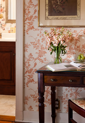 Picture of a desk with Pink flowers in a vase and the walls are covered in Pill floral design